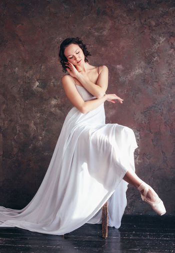 Ballet dancer ballerina in beautiful thin flying white dress is posing in dark loft studio Full Length Women One Person Young Women Young Adult Adult Real People Lifestyles Dress Leisure Activity Clothing Beautiful Woman Sitting Fashion Beauty Dancing Wall - Building Feature Elégance Skill  Hairstyle
