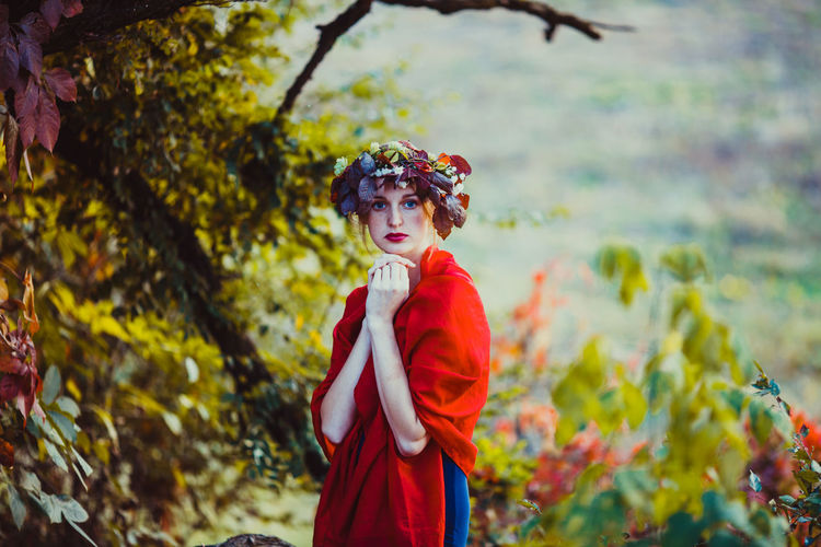 Midsection of woman with red leaves