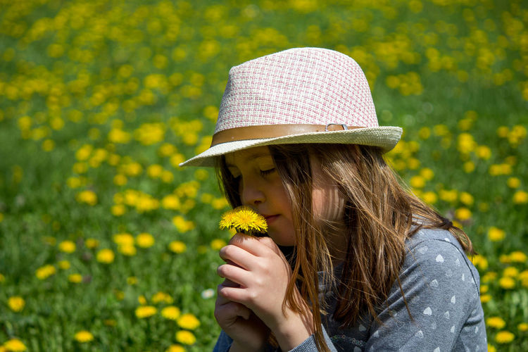 Portrait of woman with yellow flower in park