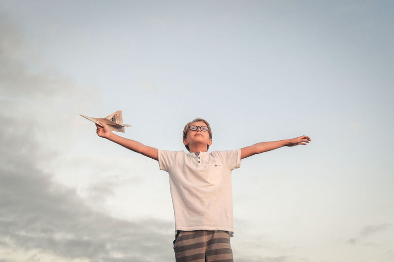 Low angle view of boy with arms outstretched holding paper airplane against sky