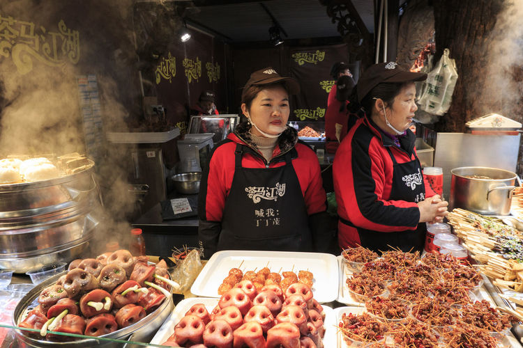 Chengdu, China - December 10, 2018: Chinese people selling street food in Chengdu Kuanzhai alley Chengdu China ASIA Food Street Food Kuanzhai Alley Pork Vegetarian Food Vegan Food Real People Food And Drink Portrait Looking At Camera Smiling Two People Waist Up Women Standing Front View