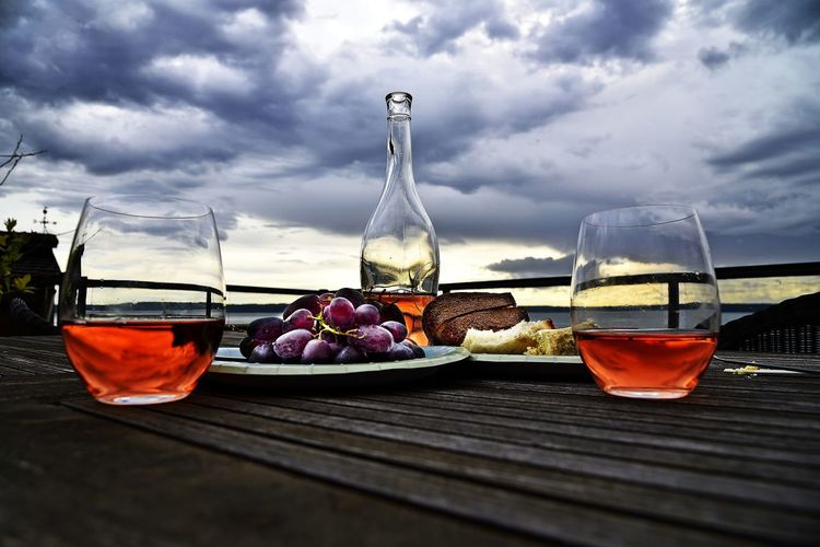 Close-up of drink and food on table against cloudy sky