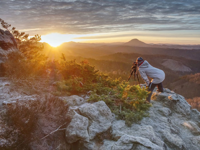 Woman art photographer works at camera on fiber glass tripod. misty spring daybreak above land