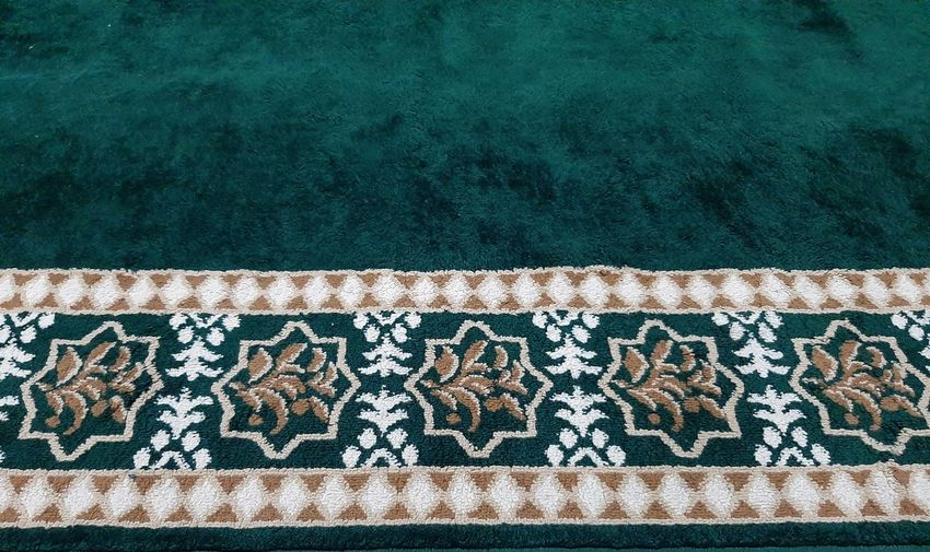 High angle view of green carpet with floral patterns