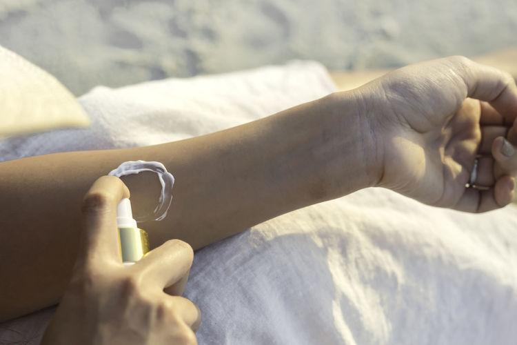 Midsection of woman applying suntan lotion