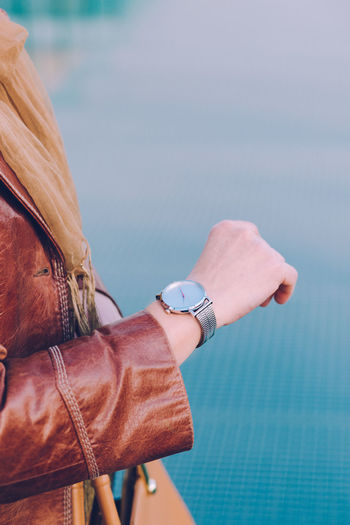 Midsection of woman checking time on wristwatch standing against blue wall