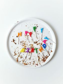 Happy Birthday White Background White Plate Dirty Plate Happy Birthday Celebration Full Frame Shot Minimalism Crumbs Wick Wax Lighted Candles Burnt Down Happy Day Baking Birthday Cake Letters Typography No People Cake Decorating Colored Birthday Candles Smeared Chocolate Light