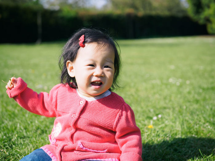 Portrait of cute girl sitting on grassy field during sunny day