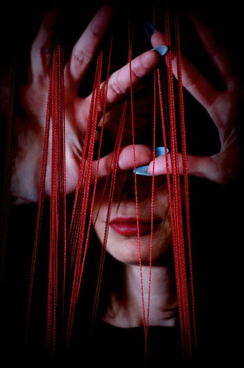 Woman Behind Tangled Threads Between Finger