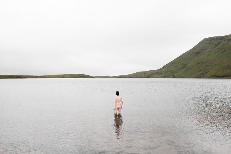 Naked Man Standing In Lake Against Sky