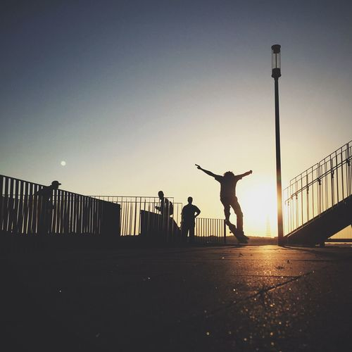 Low angle view of woman jumping at sunset