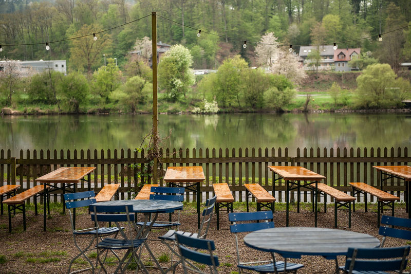 Tree Table Seat Chair Water Plant Lake No People Nature Absence Beauty In Nature Tranquility Empty Day Reflection Furniture Cafe Outdoors Food And Drink Rainy Days Wet Beer Garden Summer Light Bulbs Chain Of Lights