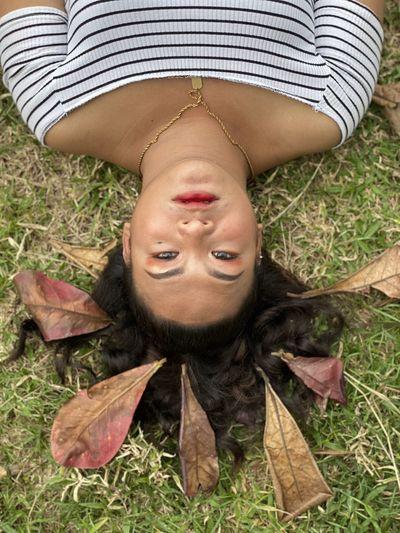 High angle portrait of woman lying on grass
