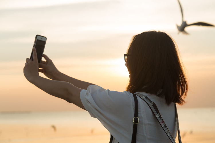 Woman taking selfie through mobile phone by sea at sunset
