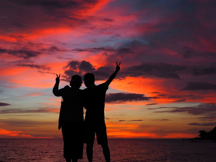 Adult Arms Raised Beach Beauty In Nature Cloud - Sky Gesturing Horizon Over Water Leisure Activity Lifestyles Love Men Nature Orange Color Outdoors Real People Scenics Sea Silhouette Sky Standing Sunset Togetherness Two People Water Women