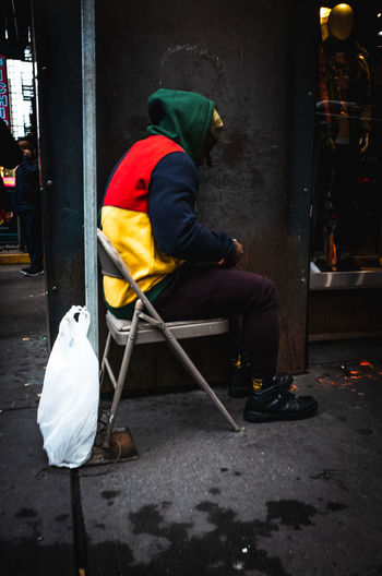 Rear view of man sitting on seat in city