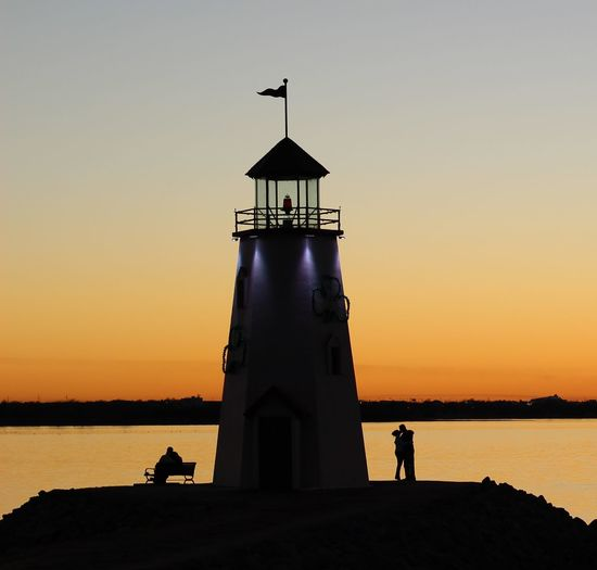 Silhouette people and lighthouse by sea against sky during sunset