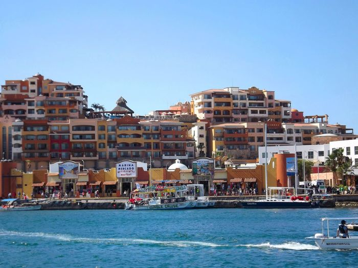 Cabo San Lucas waterfront. Architecture Blue Boat Building Building Exterior Built Structure City Clear Sky Copy Space Day Incidental People Mode Of Transport Moored Nautical Vessel Residential Building Residential Structure Sea Transportation Water Waterfront