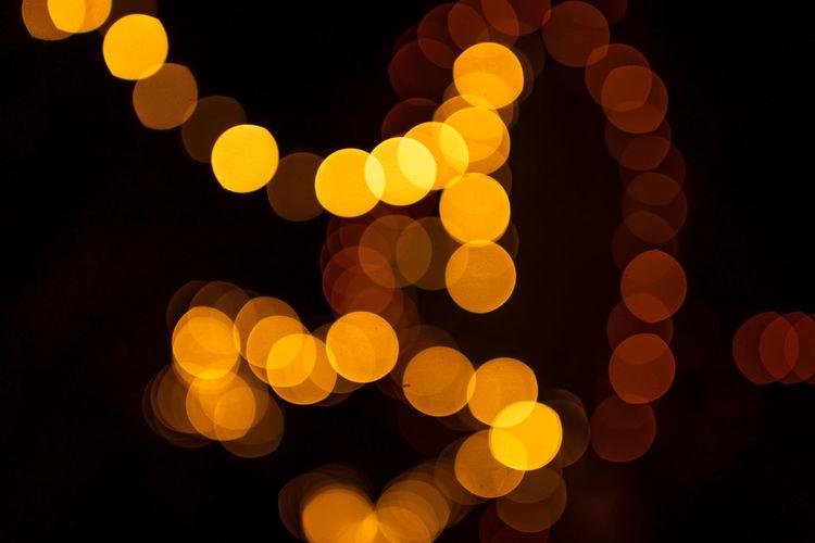 Defocused image of illuminated orange lights at night