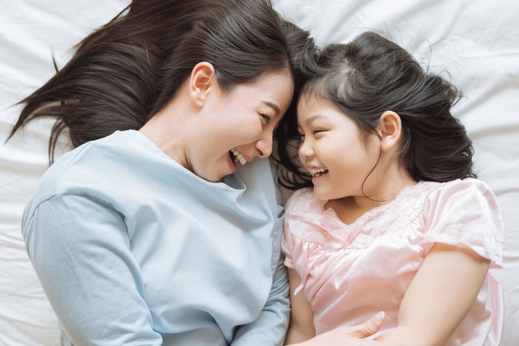 Mother and her daughter child girl playing in the bedroom .Happy Asian family Asian  Family Happiness Happy Happy People Family Time Home House Daughter Parent Father Mother Dad Mom Love Lifestyles Living Room ASIA Japanese  Korean Thai Taiwan Bedroom Bed Kiss Togetherness Child Women Bonding Females Childhood Positive Emotion Girls Emotion Furniture Smiling Indoors  Family With One Child Hair Innocence Care Smile Fun Portrait