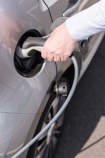 Cropped hand of man charging car at station