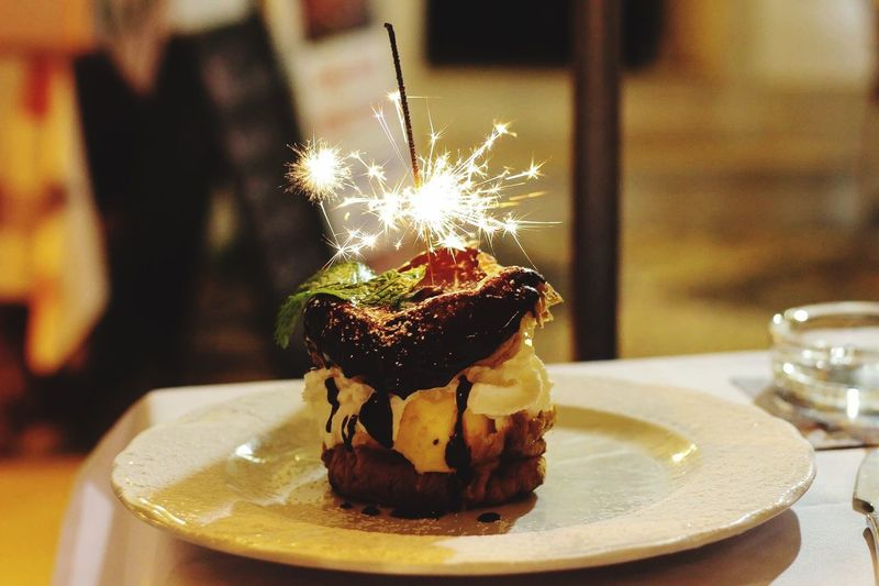 Lit Sparklers On Cake In Plate
