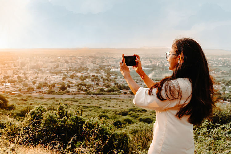 Woman photographing on mobile phone at beautiful landscape