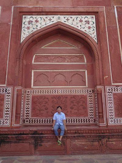 Full length of man sitting on historic building