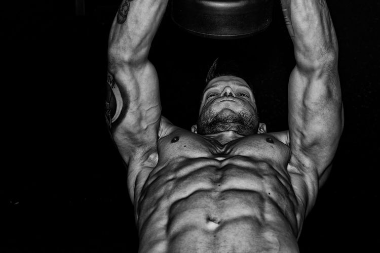 Low angle view of shirtless man exercising against black background