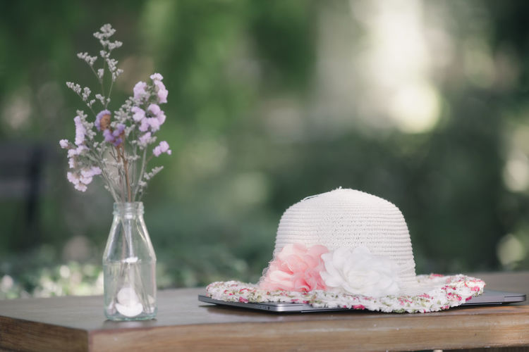 Hat that sits on my laptop on a table wooden and flower vase is my workspace in my garden house stay