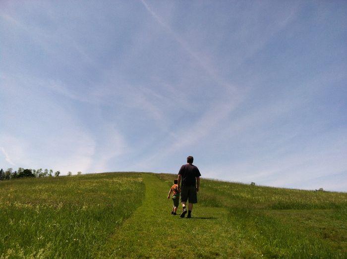 Rear view of man standing on grassy field