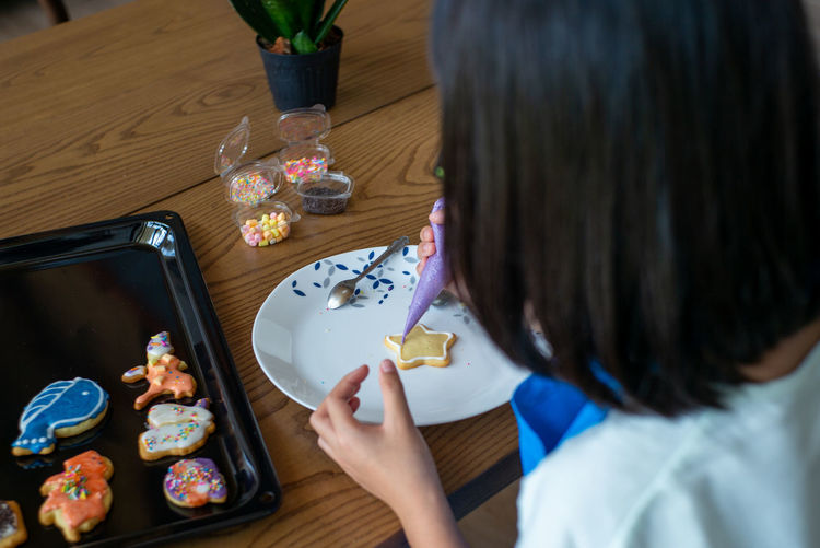 High angle view of girl icing cookies