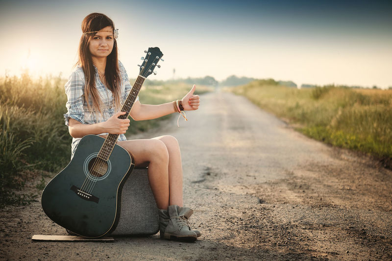 Acoustic Guitar Beautiful Woman Beauty Casual Clothing Fashion Full Length Guitar Holding Lifestyles Music Musical Instrument Musician Nature One Person Outdoors Portrait Road Sitting Sky String Instrument Women Young Adult Young Women