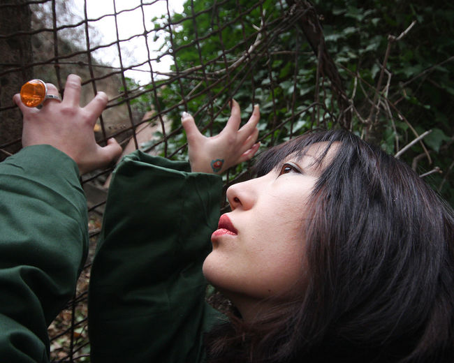 Close-up of woman looking up while holding chainlink fence