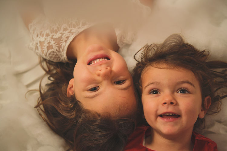 High angle view of cute siblings lying on bed