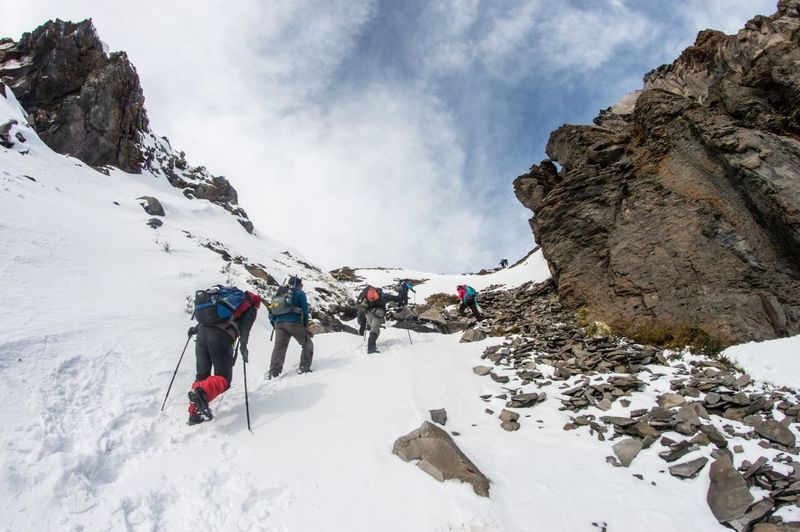 Low angle view of people hiking on snow covered mountains against sky