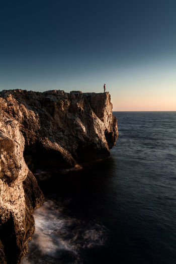Man Silhouette Beach Beauty In Nature Cliff Guidance Horizon Horizon Over Water Idyllic Land Lighthouse Nature Non-urban Scene Outdoors Rock Rock - Object Rock Formation Scenics - Nature Sea Sky Solid Sunrise Tranquil Scene Tranquility Water