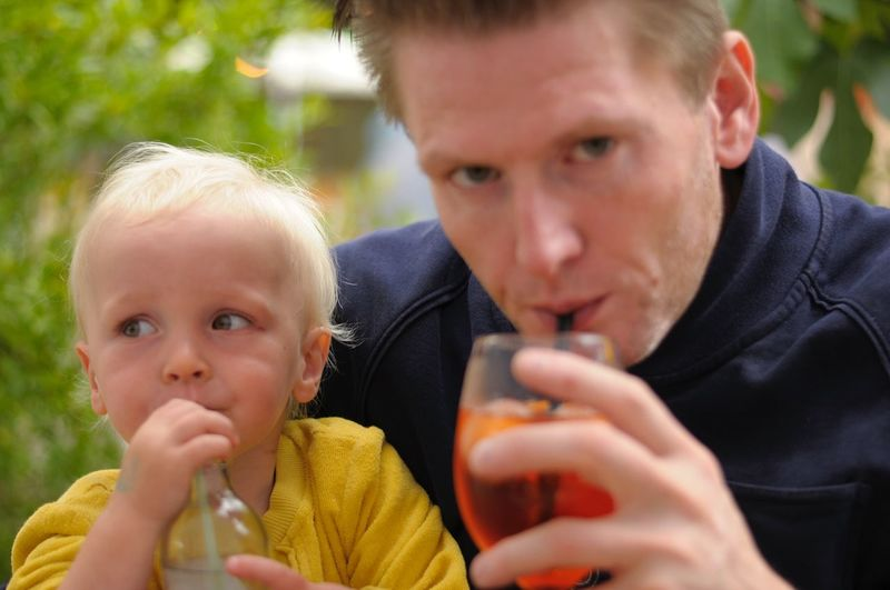 Close-Up Of Father And Son Having Drinks Outdoors