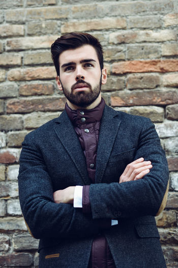 Portrait Of Young Man With Arms Crossed Standing Against Brick Wall