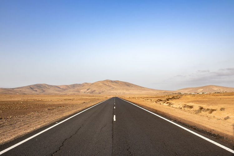 Deserted road with mountains in the background in arid landscape on fuerteventura canary islands