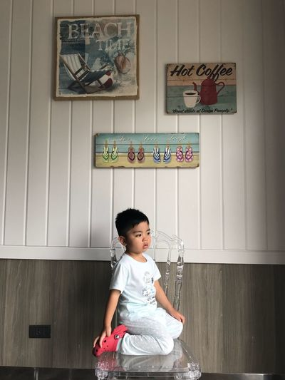 Cute Boy Sitting On Chair At Home