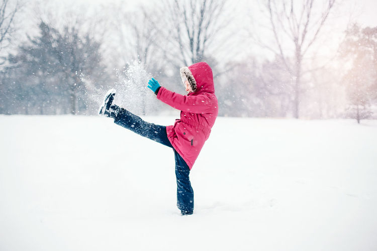 Girl kicking snow on land