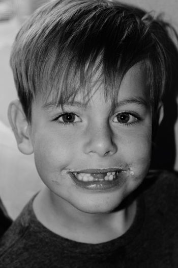 Close-up portrait of smiling boy with gap toothed at home