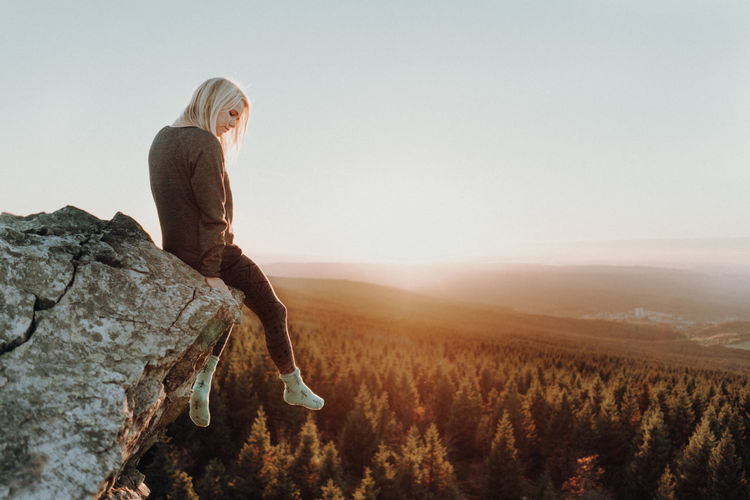 Woman sitting on cliff over forest during sunset One Person Sky Adult Land Nature Mountain Rock - Object Rock Environment Full Length Beauty In Nature Landscape Non-urban Scene Scenics - Nature Side View Day Solid Copy Space Outdoors Lens Flare Forest Cliff Sunsets Holiday Moments