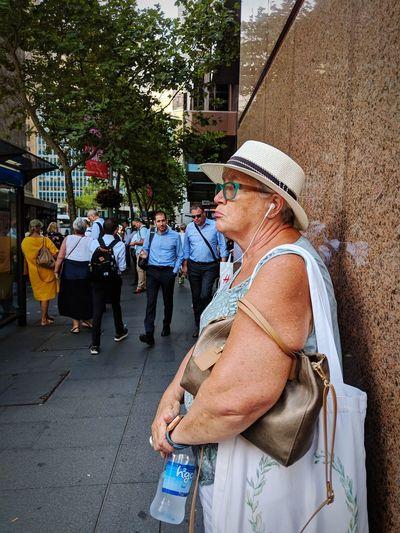 """Waiting sucks"" Expression Face waiting game Wait Patience Street Photography People Watching People Photography people and places Tree Women Headwear Men Urban Scene"