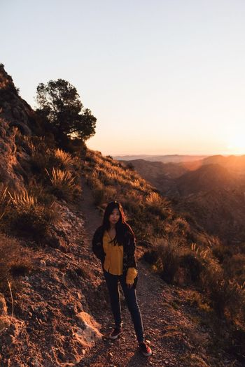 Sunrise One Person Leisure Activity Real People Lifestyles Sky Full Length Nature Standing Young Adult Beauty In Nature Casual Clothing Front View Young Women Tree Sunlight Non-urban Scene Clear Sky Sunset Outdoors