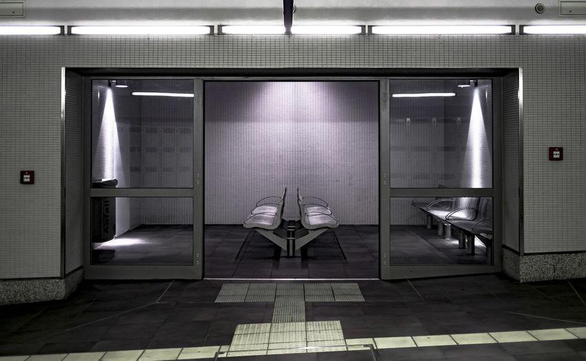 Empty chairs in waiting room seen through doorway