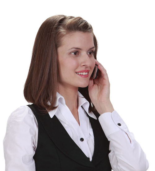 Portrait of a young woman on a phone against a white background. Front View One Person Portrait Young Adult Looking At Camera Smiling Phone Telephone Communication Young Woman Young Woman Smiling Businesswoman Woman Using Phone Woman On The Phone Call Phone Call White Background Isolated Isolated On White Studio Shot Happiness Adult Cut Out Business Person