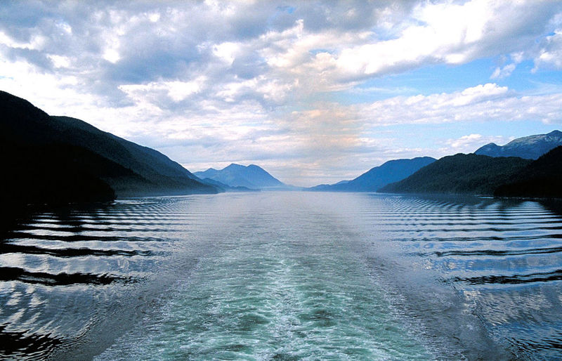 View from stern of cruise ship - Alaskan Fjords Alaska Beauty In Nature Cruise Ship Mountain Outdoors Scenics Sky Water Ripples In The Water Narrow Waterway Distant Mountains Blue Sky White Clouds