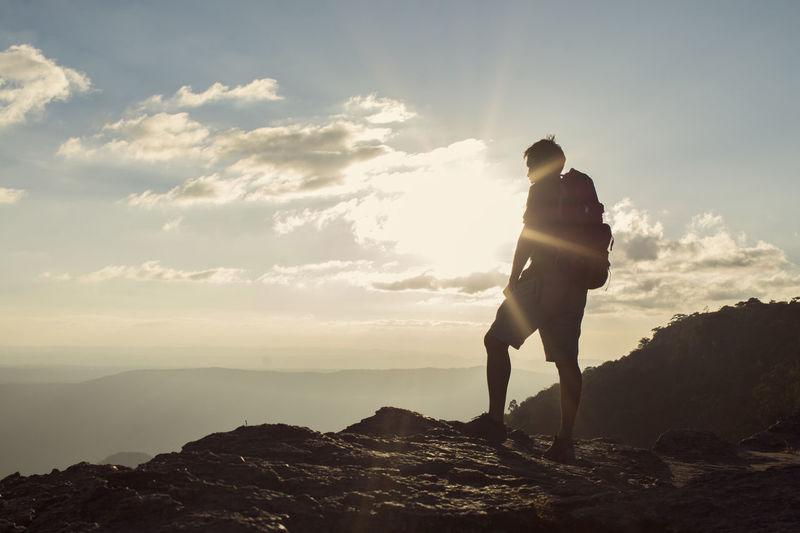 Full length of silhouette man standing on rock against sky